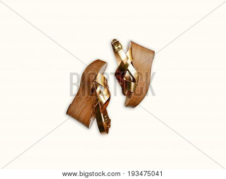 Gold leather trendy woman sandals isolated on bright background. Fashion top view style, summer platform shoes.