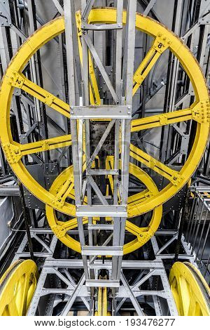 Yellow machinery wheels with metal silver construction pieces and cables at Barcelona's port cable car vertical