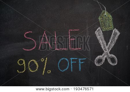 Sale 90% off. Sale and discount price sign with scissors cutting price tag drawn with chalk on blackboard