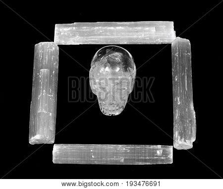 Natural white selenite rods and clear quartz skull on black background