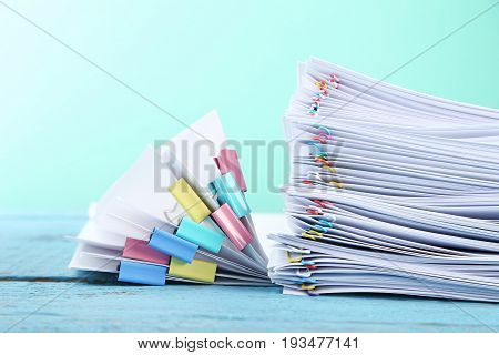 Stack Of Papers With Paperclips And Clamps On Blue Wooden Table