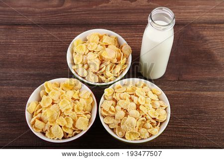 Cornflakes In Bowls And Bottle Of Milk On Wooden Table