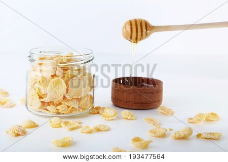 Cornflakes In Glass Jar With Bowl Of Honey Isolated On A White