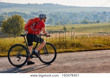Ecotourism in Europe. Bicycle race in the country. Bicyclist traveler with backpack has adventure on european country road. Cyclist in white helmet and red t-shirt rides black mountain bike.