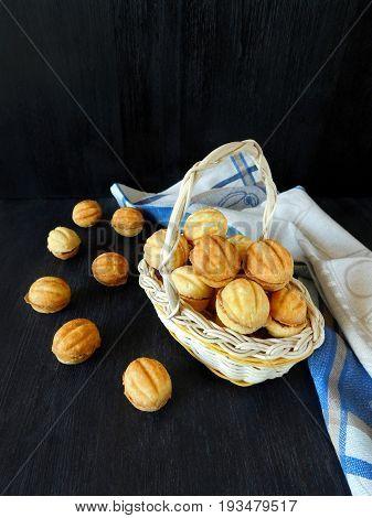 Walnut shaped cookies in a wicker basket on a dark background