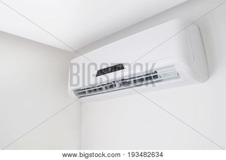 White split air conditioner on a white wall. Home interior in a small apartment