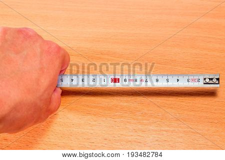 The hand holds the tape measure on a wooden background is a very convenient tool for measuring the length of the width and height as well as the distance