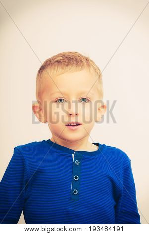 Face expressions children concept. Portrait of happy kid boy looking straight to camera