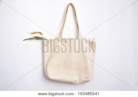 Mock up of linen bag against hanging on white wall.