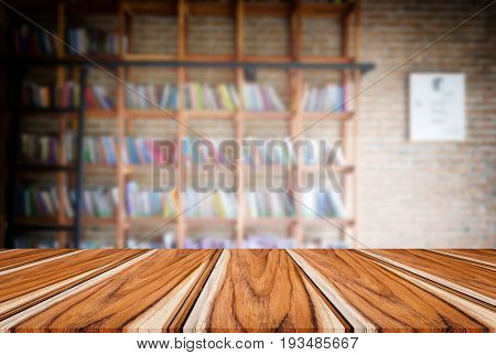 Selected focus empty old wooden table and Library or Bookstore blur background with bokeh image. for your photomontage or product display.