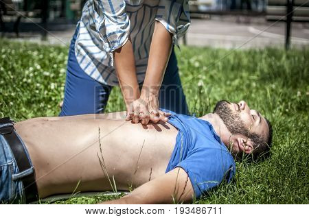 girl making cardiopulmonary resuscitation to an unconscious guy after heart attack