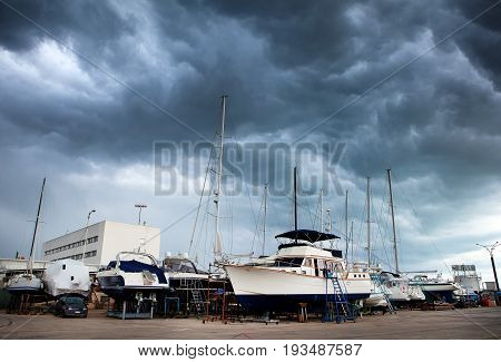Sailing boats and motor boats in the shipyard for repair and maintenance in the Marina with a gloomy stormy sky