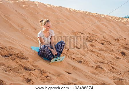 Young Woman Rolls On A Toboggan In The Sledge In The Desert