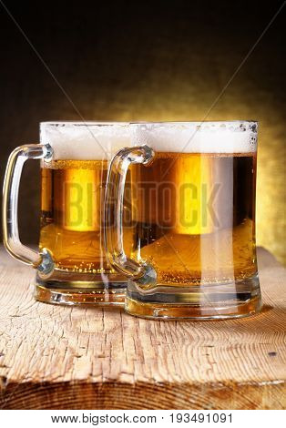 two Glasses of beer on wood background