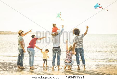 Happy families group with parents and children playing with kite at beach vacation - Summer joy happiness concept with mixed race people having fun together at sunset - Warm vintage backlight filter