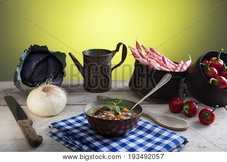 A bowl of minestrone soup and other vegetables on the table