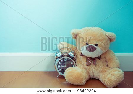 Teddy bear holding the shiny clock time is up time is limited concept and idea blue pastel wall background