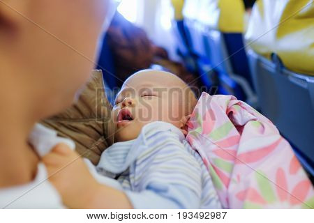 Adorable Baby Sleeping On Airplane Toddler boy sleeping on father's laps while traveling in airplaneFlying with children. Dad and sleeping 10 months old baby Dad holding son:Shallow depth of field