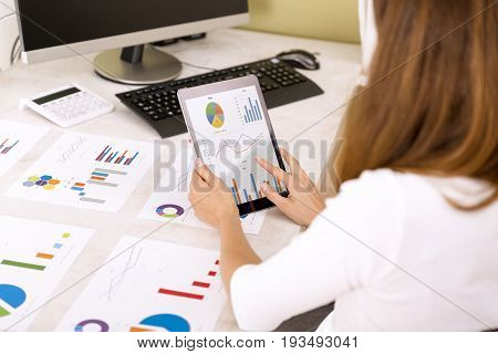 Young business woman reviewing sales results on tablet. Graphs on office table