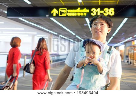 Smiling asian father holding Cute little Asian teething 1 year old baby boy child in a baby carrier Dad and son standing near sign at airport Traveling with kid concept / Selective focus