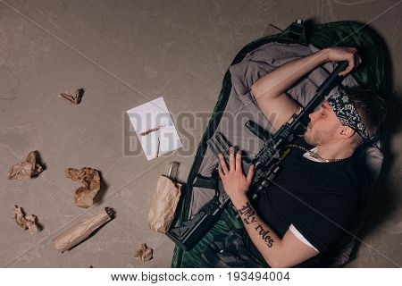 Soldier is sleeping with a rifle. Bad habits. Cigarette, alcohol, weapon top view. Careless lifestyle, gang war, social problem, negative addiction concept