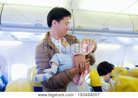 Tenderness. Young father is lulling asian cute baby boy during flight on commercial airplane. Concept photo of air travel with baby: Shallow depth of field