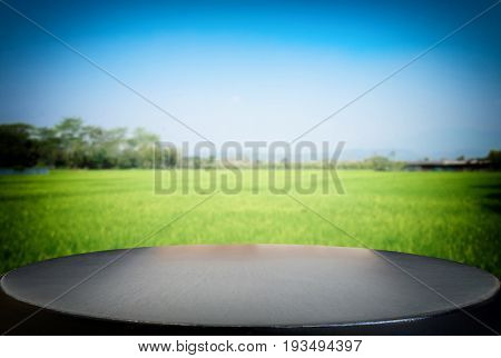 Selected focus empty black wooden table and cornfield or meadow blur background with bokeh image. for your photomontage or product display.