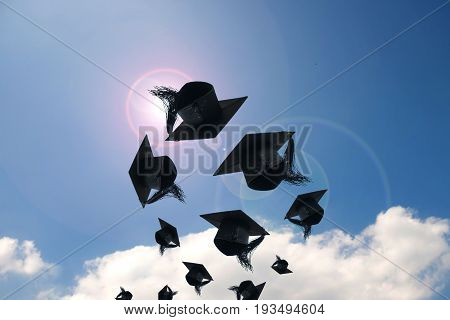 Graduation day Images of graduation Caps or hat throwing in the air with sunshine day on blue sky background Happiness feeling Commencement day Congratulation Ceremony.