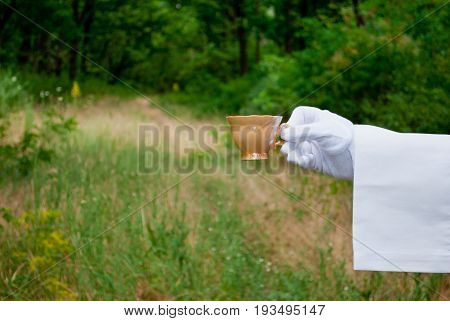 The waiter's hand in a white glove and with a white napkin holds an empty pink beige small coffee cup on a blurred background of nature green bushes and trees