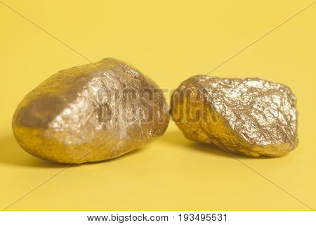 Golden Nuggets On A Yellow Background .