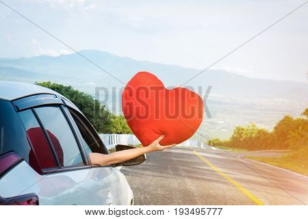 Relaxed happy traveler Young beatiful asian gilr holding big red heart and Reach out of the car at sunset and beautiful view with mountain road background.