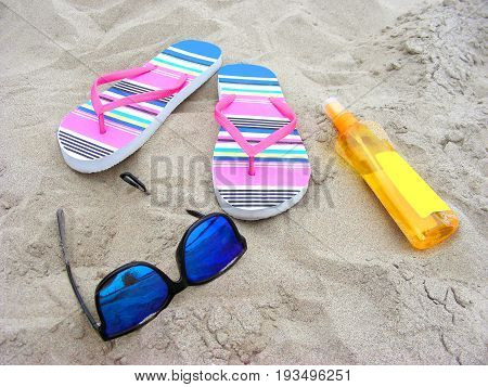 Summer time on a sandy beach with sunglasses flip-flops and sun-care milk
