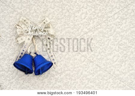 blue jingle bells with a silver ribbon bow and merry christmas writing on a silver background