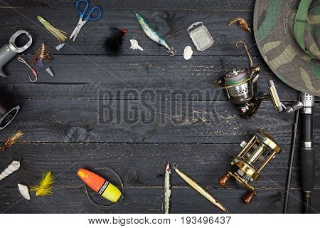 Fishing rods and reels fishing tackle on black wooden background