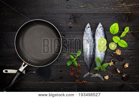 Fresh Lungtail Tuna fish and black frying pan on dark black background Fish with spices and vegetables cooking background concept