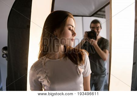 Photo session backstage. Photographer shoot woman. Back view from model's shoulder on studio interior and man, who work with camera