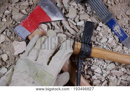 Axe gloves and construction tools on pile of rubble