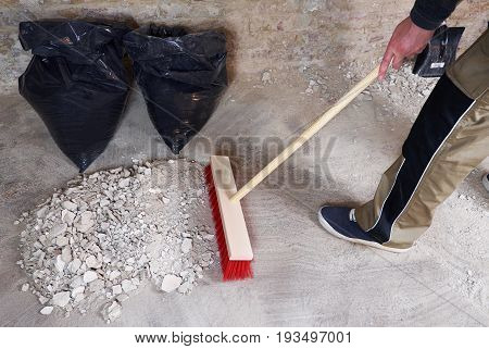 Worker sweeping the rubble with red broom
