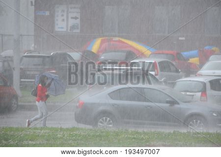 KOROLEV, MOSCOW REGION, RUSSIA - JUNE 30, 2017: Unidentified Caucasian woman walks under umbrella while it hails