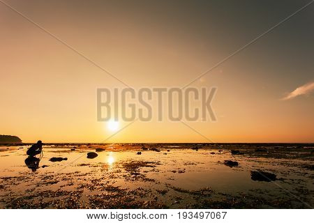 professional photography man take a photo sunset dramatic sky over the tropical sea
