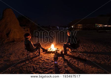 Couple Sitting At Burning Camp Fire In The Night. Camping In The Desert With Wild Elephants In Backg