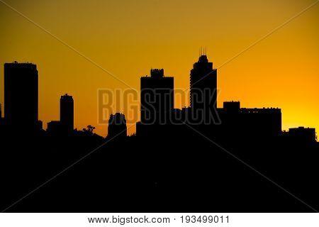 Silhouette of city skyline against orange setting sunset