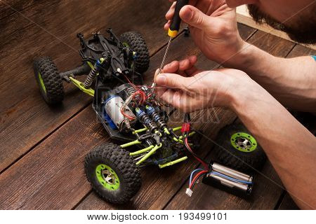 Rc radio control car crawler model toy electronics repair. Green toy suv in repairshop workplace, free space