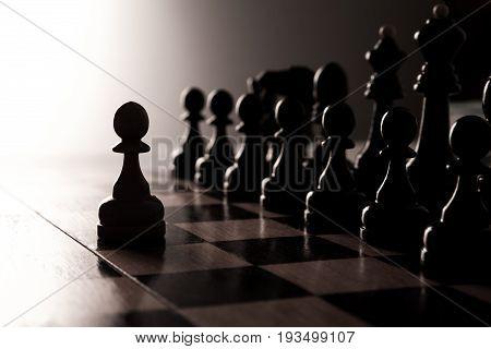 Big black chess pieces set close-up dark background