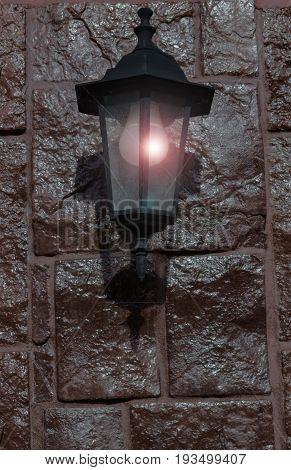 Burning a dim lantern on a dark stone wall