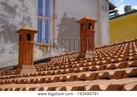 Beautiful orange colors of terracotta roof tiles and chimneys of a rooftop in Portovenere Italy