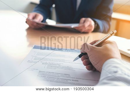 Executive reading a resume during a job interview and businessman Completing Application Form. Hiring concept.