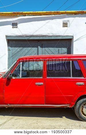 Red retro car on a background of wooden gates.