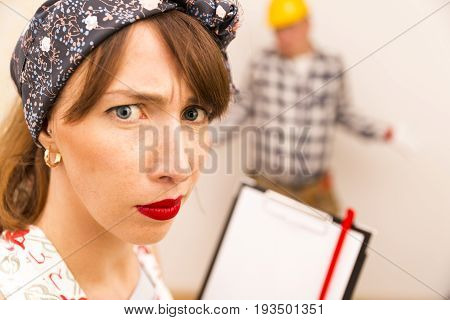 Angry housewife giving orders to handyman for house chores