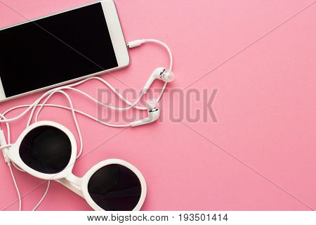 studio shot of white sunglasses smart phone and earbuds on pink background